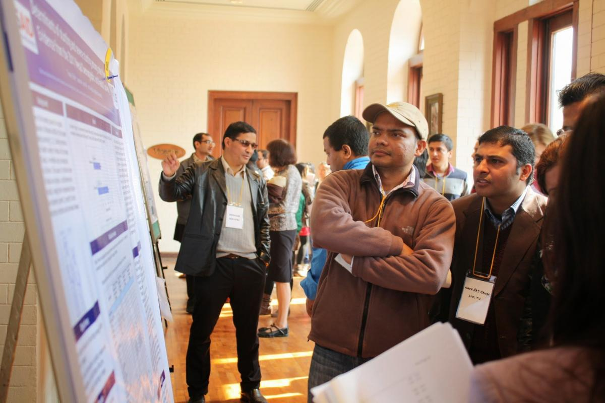 attendees at the symposium look at a poster