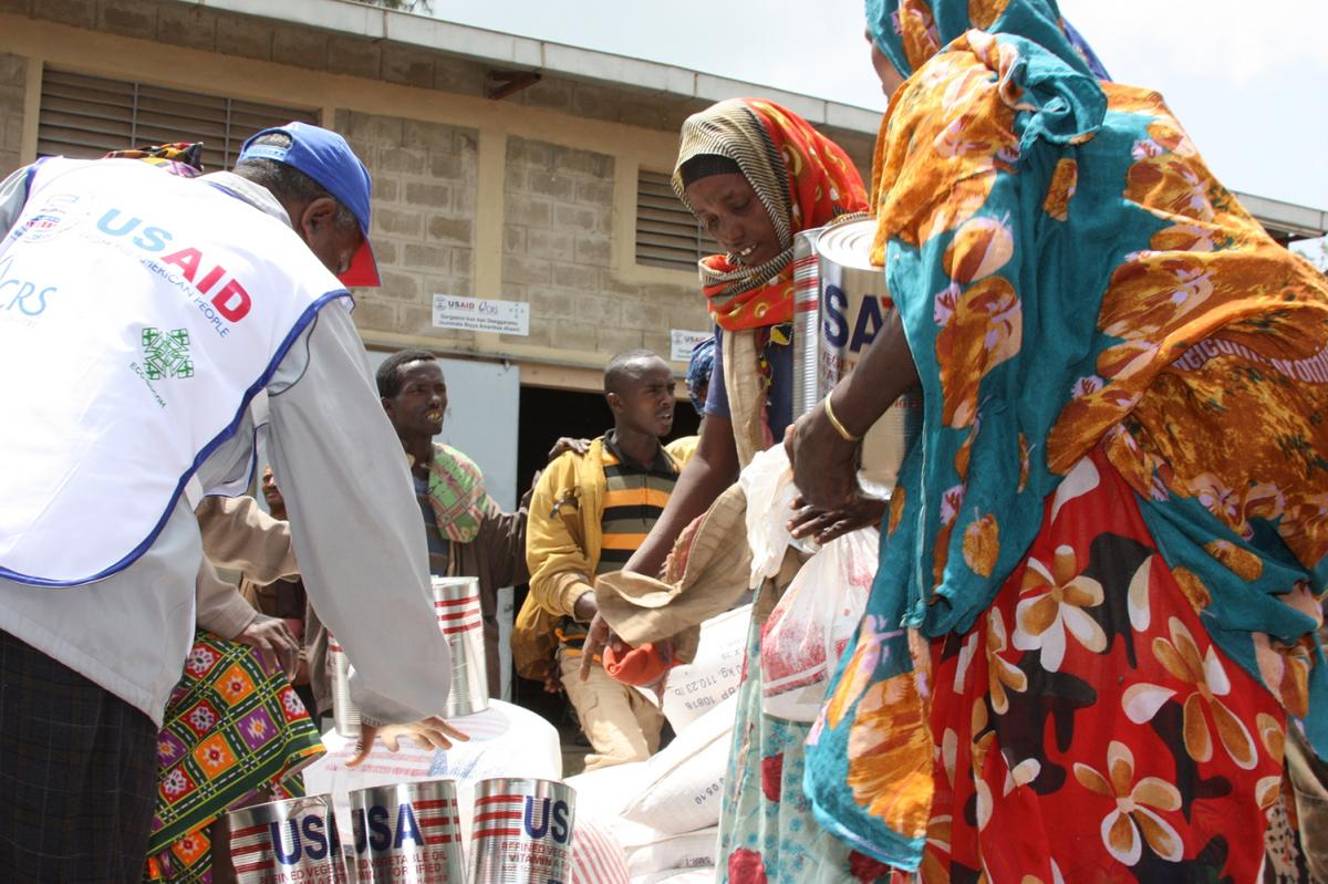 ladies in colorful dress receiving canisters and bags of food aid